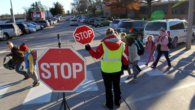 A traffic guard stops traffic for children on Oliphant Street outside West Branch Middle School and Hoover Elementary on Thursday, Nov. 19, 2015.