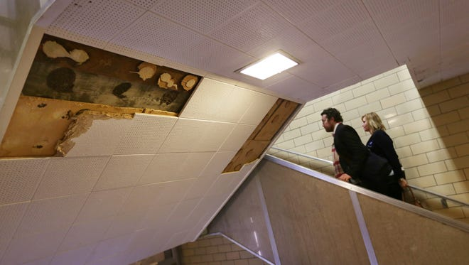 Pam Barnes, right, and Asher Huey of the American Federation of Teachers walk by missing ceiling tiles while touring Osborn Collegiate Academy of Mathematics Science and Technology on Thursday, Jan. 14, 2016.