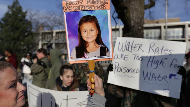Amanda Hughes, 36, of Flint holds a photograph of her seven-year-old daughter during a rally in downtown Flint on Monday, January 25, 2016 where about 100 people demanded not to have to pay for water that was tainted with lead. Romain Blanquart/ Detroit Free Press