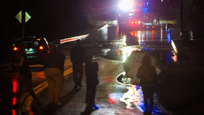 Bystanders watch as emergency crews respond to a water rescue for a car submerged in floodwaters on Freysville Road at Kreutz Creek in Hellam Township on Wednesday. No injuries were reported but at least one family in a nearby mobile home park evacuated as a precaution. A storm on Wednesday swept across much of York County, knocking out power and trees.
