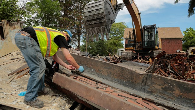 A DEQ asbestos inspector takes samples while looking over a two-story apartment building owned by the city of Detroit being torn down at the corner of E. Grand Blvd. and McDougall in Detroit on Wednesday June 24, 2015.