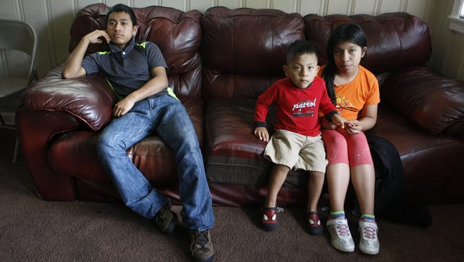 Melisa Jimon Reynoso (right) and her 3-year-old brother, Brian Jimon Reynoso, sit with Candelario Jimon Alonzo at their home in Memphis, Tenn. The 16-year-old joined his relatives when he arrived in Memphis after fleeing Guatemala.