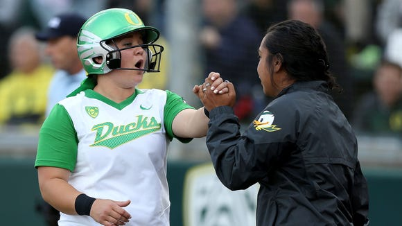 Oregon's Hailey Decker, left, celebrates after scoring in the fifth inning of a softball hosts BYU for their NCAA Regional game on Thursday, May 14, 2015, in Eugene, Ore.