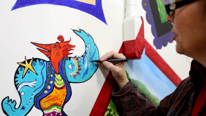 Debby Denno works on a mural outside the Red Raven Gallery in downtown Salem. The gallery will close May 21.