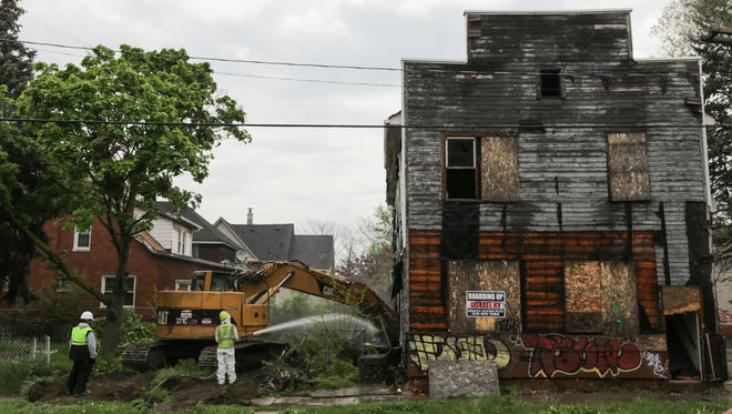 City of Detroit Construction Services workers tear down an abandoned structure across from Bennett Elementary School in Detroit on Thursday May 12, 2016. Teachers, parents and community organizers pushed to have vacant buildings demolished near the school in southwest Detroit worried when body was found in the vacant rooming house across from school
