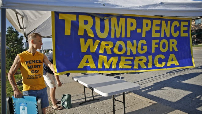 Pascal Le Guellec prepares to move a banner at a pop-up protest against Donald Trump and Mike Pence on Capitol Ave., Thursday, September 1, 2016.  He and Kevin Warren sold signs and bumper stickers at the corner of 15th and Capitol until asked not to block the sidewalk by police.  They are with the Pence Must Go Action Committee.
