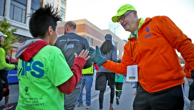 Carlton Ray, right, congratulates 5K runners at the finish line during the CNO Financial Indianapolis Monumental Marathon, Saturday, November 5, 2016.  He is the race founder.  He also congratulated half marathon and marathon racers, as well as fun run runners.