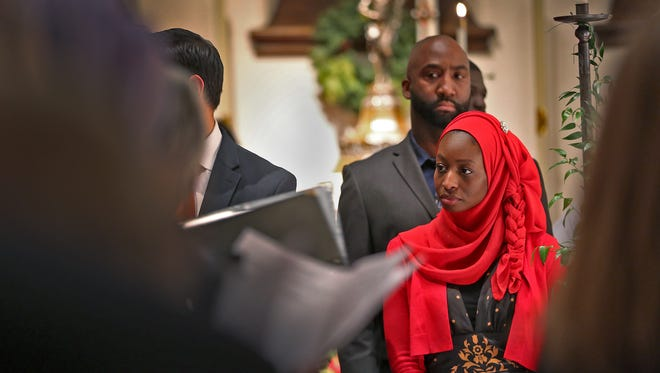 Members of the Indianapolis Muslim Community Association, including Yaseen Al-Khattab and Halima Al-Khattab, in the red hijab, watch the processional of the Christmas Eve service at Christ Church Cathedral, December 24, 2016.  The Cathedral celebrated Christmas Eve with Indianapolis Muslim friends.