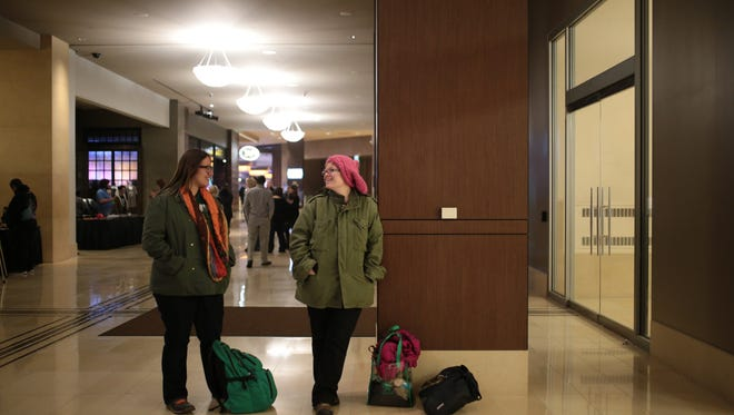 Seven Mattes, 32, left, and Lisa Sutton, 32, both from Lansing, MI wait inside the MGM Grand Casino lobby on Friday, January 20, 2017 in Detroit in hopes for a bus to show up to give them a ride to the Women March in Washington. After sending $K to a bus company in Pennsylvania and the bus not showing up, they think it was an Internet swindle.