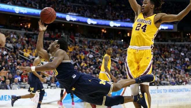 Michigan guard Derrick Walton Jr. (10) is tripped by Minnesota forward Eric Curry (24) while shooting the ball in the second half of U-M's 84-77 win over Minnesota in the Big Ten tournament semifinal Saturday in Washington.