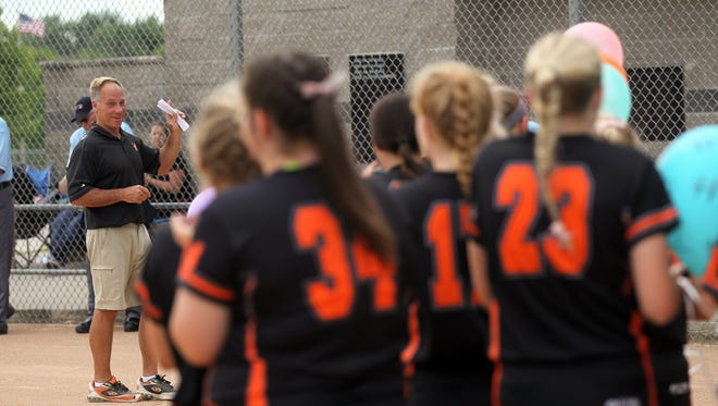 Solon head coach Jim White receives balloons from players in recognition of his recent national softball coach of the year award before their game against Maquoketa in Solon on Thursday, June 22, 2017.