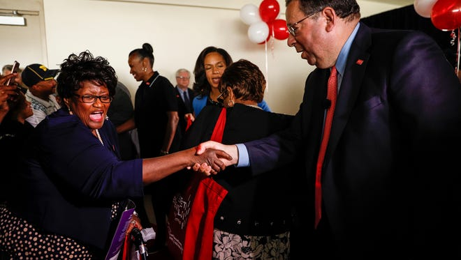 David L. Cohen, senior executive Vice President and Chief Diversity Officer of Comcast Corporation, right, shakes hands with Grace Shannon after giving her a free laptop at the Joseph Walker-Williams Community Center in Detroit, Wednesday, August 23, 2017.