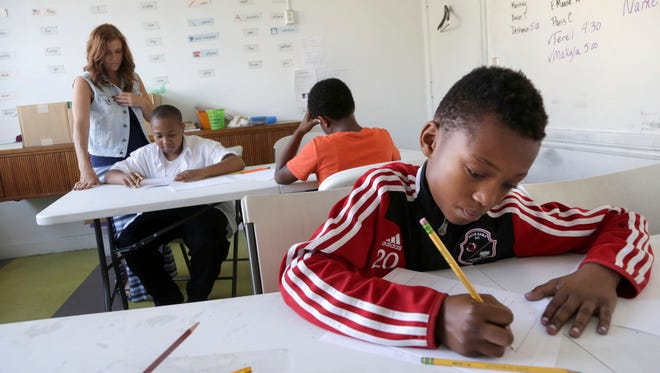 From left, Amy Mullins, 47, of Northville, a tutor and life coach, helps Marco Archer, 13, of Detroit, Jacob Wilbourn, 11, of Detroit and DeShawn Beal, 13, of Detroit as part of the after school programs that include tutoring and exercise at the Downtown Boxing Gym in Detroit on Friday, Sept. 22, 2017.