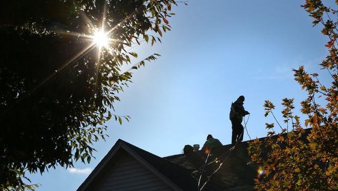 Members from Green Alternatives Inc. install a solar panel system in Carmel, Tuesday, October 31, 2017.