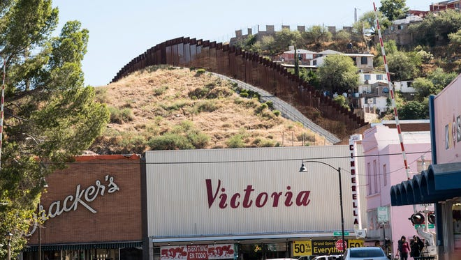 The U.S.-Mexico border fence can be seen behind Bracker's Department Store in Nogales, Arizona. The decades-old store shut its doors in October amid declining traffic from Mexican shoppers.