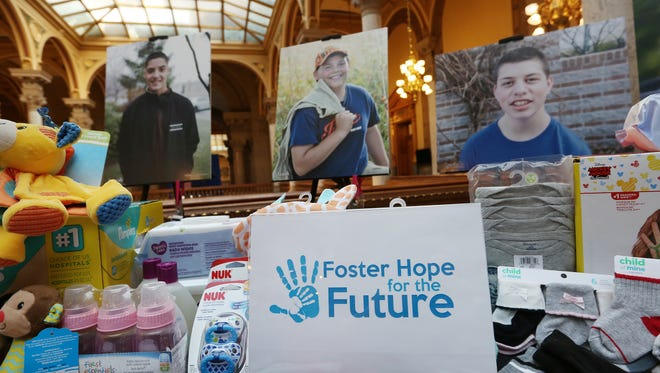 Donations and photos of children up for fostering or adoption, are seen during a press conference introducing this session's partnership between lawmakers and Indiana Association of Resources and Child Advocacy (IARCA) to help Indiana's foster families and foster children, on Organization Day at the Indiana Statehouse, Tuesday, Nov. 21, 2017.