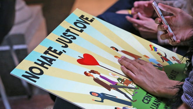 Supporters for hate crime legislation hold signs for love, not hate, during a rally of supporters for a hate crime law, on Organization Day at the Indiana Statehouse, Tuesday, Nov. 21, 2017.
