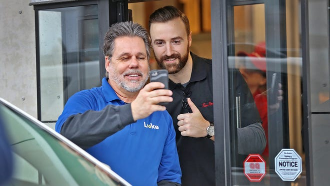 Mark Ellis stops for a selfie with Indy Car driver James Hinchcliffe who was working the drive-through window at the new Tim Hortons at 8301 Rockville Rd. in Indianapolis, Monday, Jan. 22, 2018.  The Canadian coffee and doughnut chain opens fully on Jan. 25, 2018.  In advance of that, there are several charity events planned.