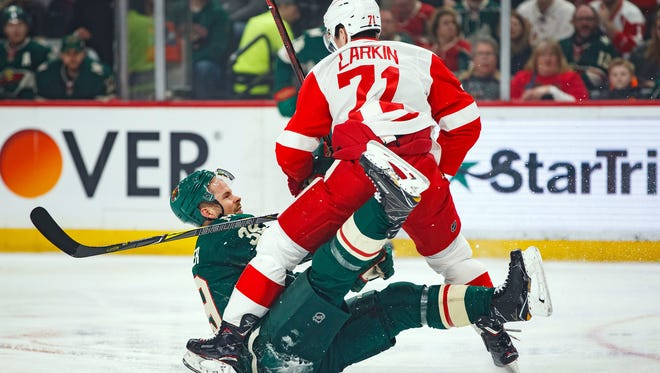 Detroit Red Wings forward Dylan Larkin (71) and Minnesota Wild defenseman Nate Prosser (39) get tangled in the first period at Xcel Energy Center on Sunday, March 4, 2018.