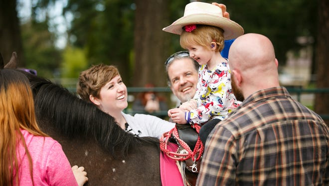 Penelope Butler smiles as she rides her new horse Cappy on Saturday, March 10, 2018. Her mother Jessica, left, and father Max, far right, stand either side of her. Make-A-Wish and local volunteers came together to donate a horse to 3-year-old Penelope, who has been diagnosed with a rare blood disorder.