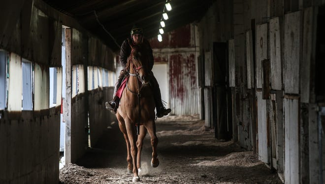 Outrider Teri Elliott, 65, of Davisburg, exercises a horse looping around an abandoned stable at the closed Hazel Park Raceway on Wednesday, April 11, 2018.