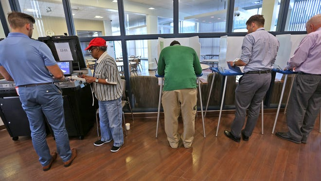 Precinct Judge Marvin Young, second from left, helps a voter as other voters continue voting at the John J. Barton Annex Apartments site, in downtown Indianapolis, for the primary election, Tuesday, May 8, 2018.