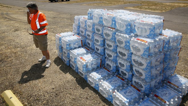 Robin Jennings from public works wipes sweat from her face while passing out bottled water at a water distribution site at the Oregon State Fairgrounds in Salem, Oregon, on Wednesday, June 6, 2018.