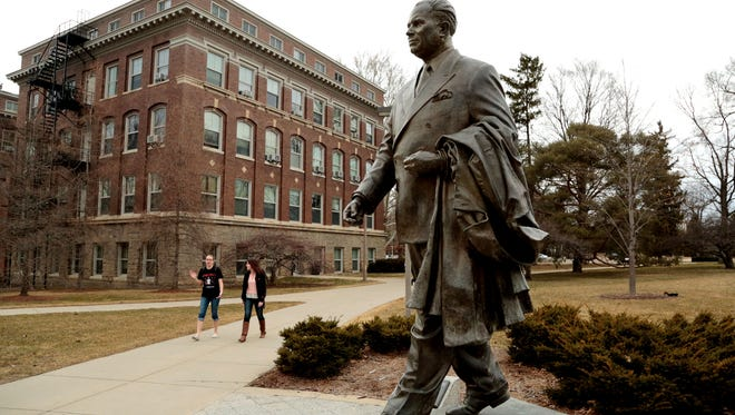 Students walk past the statue of John A. Hannah, MSU's 12th president, on the Michigan State University campus in East Lansing in 2015.