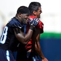 Titans outside linebacker Brian Orakpo (98) gives quarterback Marcus Mariota (8) a hug and shares a laugh as they move to the next practice period.