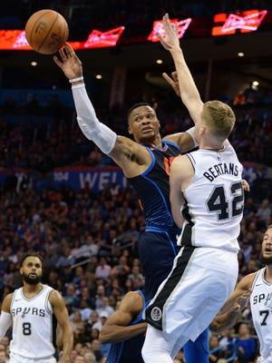 Oklahoma City Thunder guard Russell Westbrook passes the ball behind San Antonio Spurs forward Davis Bertans.