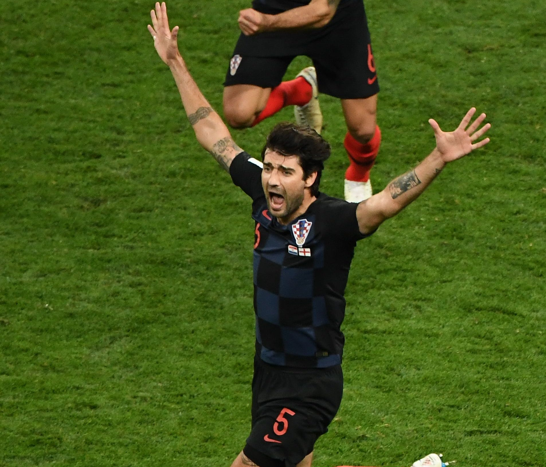 Croatia defender Vedran Corluka (bottom) and defender Dejan Lovren (top) celebrate after winning beating England to advance to the World Cup final.