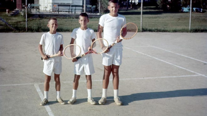 The McGrath brothers, from left to right, Randy, Rolly and Barry, on the Hughes clay courts with the Topeka Tennis Club stand in the background.