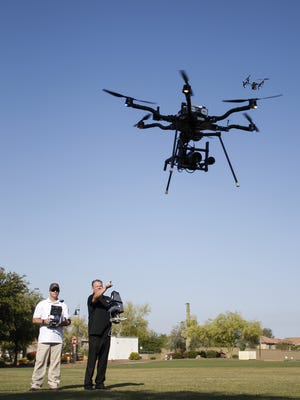 Chief pilot and business partner Travis Buchmann, from Buckeye, and Mark Taylor, from Phoenix, operate drones at the Anthem Community Park on June 8, 2016. Taylor, owner of Extreme Aerial Productions, is one of two licensed commercial drone pilots in Arizona. He first used his drone to assist with a business partner's listing by shooting aerial footage. In addition to real estate, he also shoots promo and movie work and commercials.