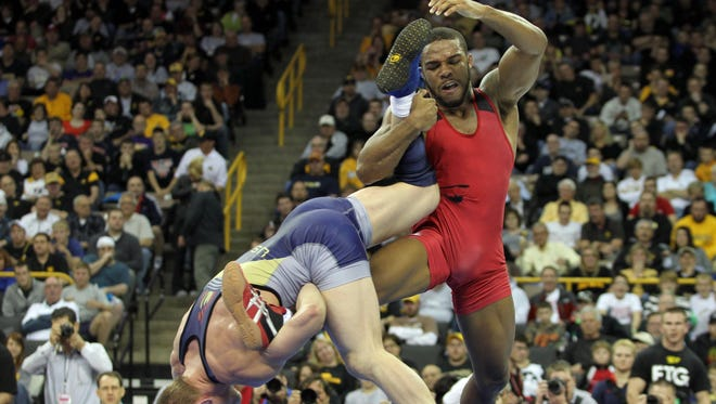 Jordan Burroughs (red) tries to avoid the takedown from Andrew Howe (blue) during the 74kg freestyle match at Carver Hawkeye Arena in 2012.