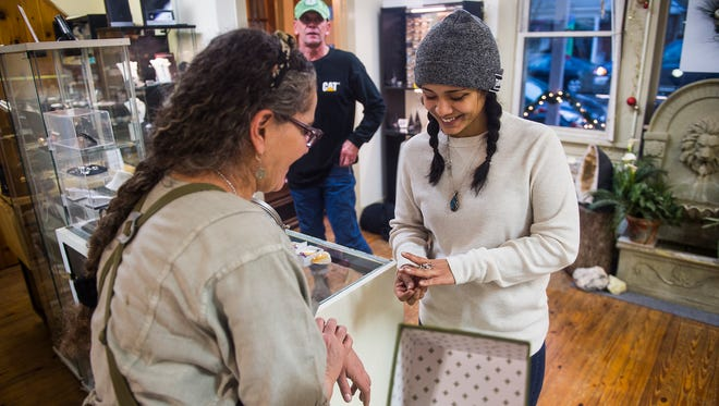 Alana Rinehart, of Glenville, talks to Marcia Fowler, owner of New Oxford Body and Soul Boutique, about a piece of jewelry at the shop on York Street in New Oxford on Dec. 23, 2015.
