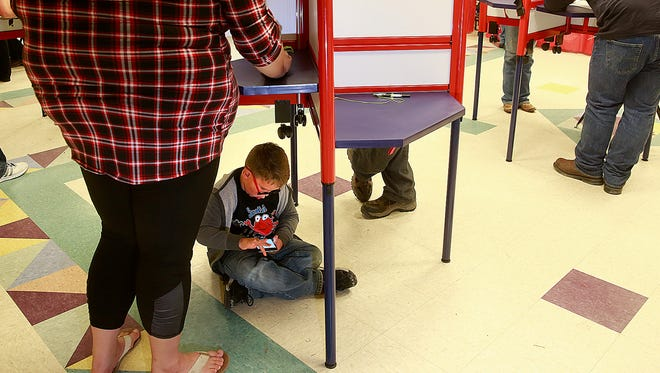 Dominic Aagesen, 6, plays a video game while his mom, Ashley Miller, votes on Tuesday at the Farmington Museum at Gateway Park.