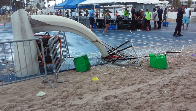 Glass is scattered around a toppled basketball hoop after a waterspout made landfall at Fort Lauderdale Beach on May 25, 2015.