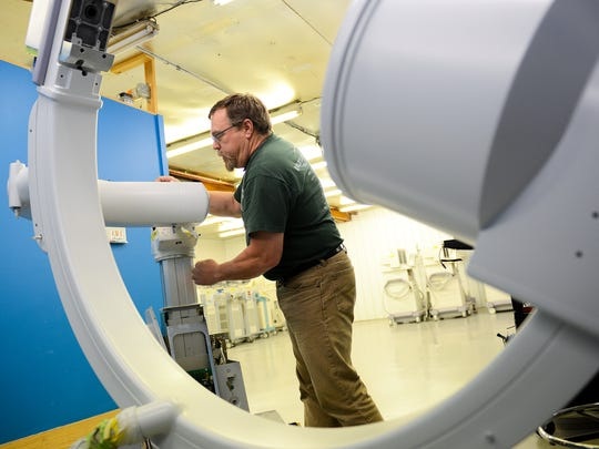 Gary Strpko, a C-Arm engineer, services one of the machines, which is a portable X-Ray machine, at  Block Imaging Thursday, Nov. 3, 2016 in Holt.