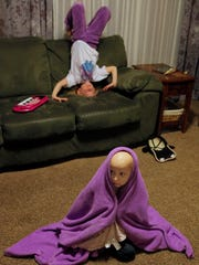 Amanda wraps herself in her favorite purple blanket as her sister, Jessica, plays on the couch behind her.