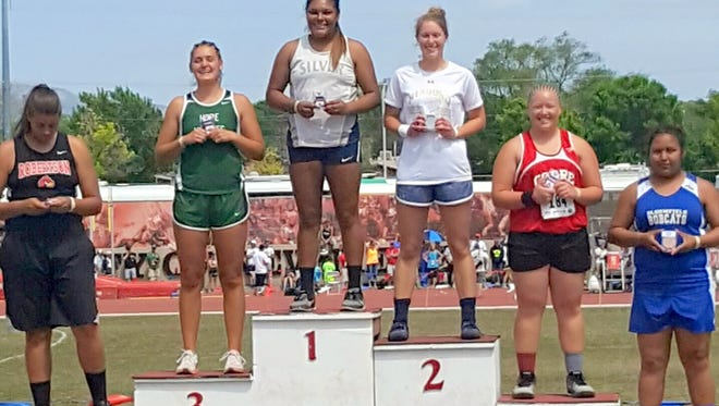 Aysia Salas stands on the podium after accepting her championship medal. She won the shot put at the state tourney in Albuquerque.