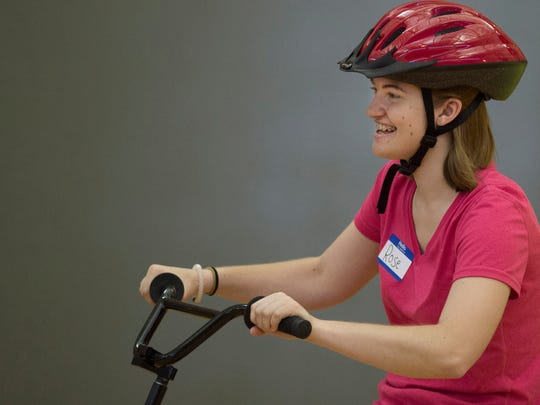 Rose Schreiner, 19, of Henderson, Ky., gets a turn on the tandem bike with Jeff Sullivan taking a back seat at the National Guard Armory during the iCan Bike camp Tuesday morning.