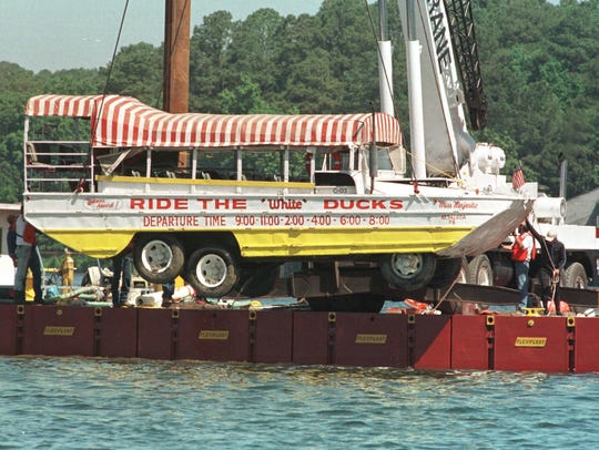 """The amphibious tourist boat """"Miss Majestic"""" that sank on Saturday, May 1, 1999 in Lake Hamilton near Hot Springs, Arkansas, leaving 13 dead, is hoisted by a crane out of the lake on Sunday, May 9, 1999. (AP Photo/Mike Wintroath)"""