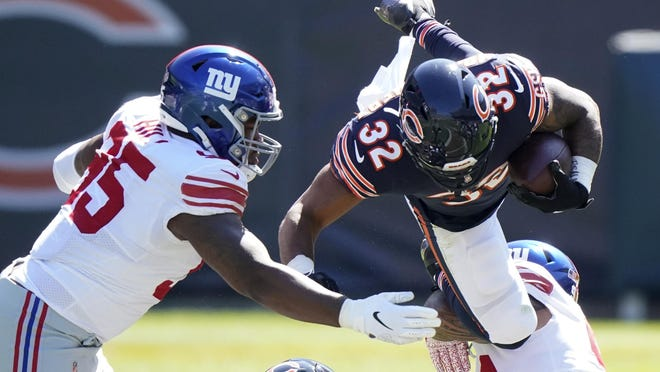 Chicago Bears running back David Montgomery (32) is brought down by New York Giants nose tackle Austin Johnson (98) as defensive end B.J. Hill (95) assists during the first half of a game in Chicago on Sunday, Sept. 20.