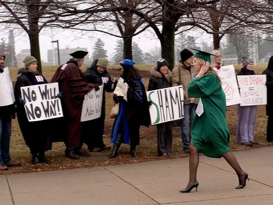 MSU graduating students walk by people protesting the selection of George Will as the keynote speaker at commencement Saturday, Dec. 13, 2014.