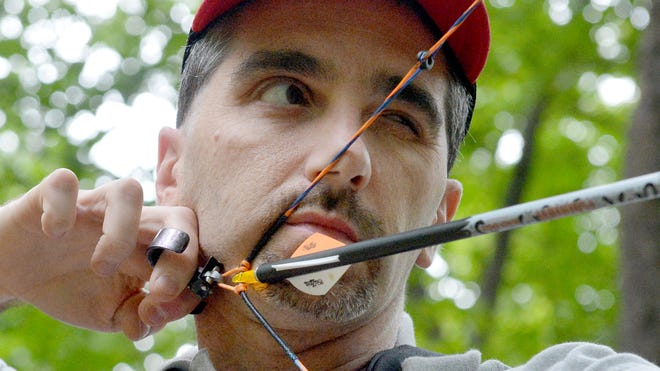 Dave Pyle of Goochland County eyes the target as he prepares to take his next shot. He joins friends following the designated course of targets during Augusta Archers 3-D archery shoot near Staunton on Saturday, August 23, 2014.