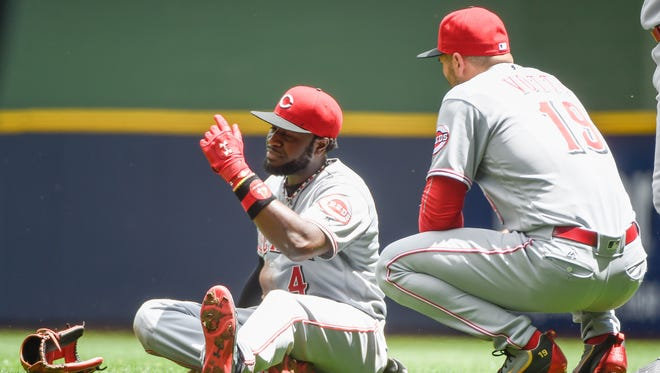 Cincinnati Reds second baseman Brandon Phillips (4) is helped by first baseman Joey Votto (19) after catching a foul ball in the first inning during the game against the Milwaukee Brewers at Miller Park on Sunday.