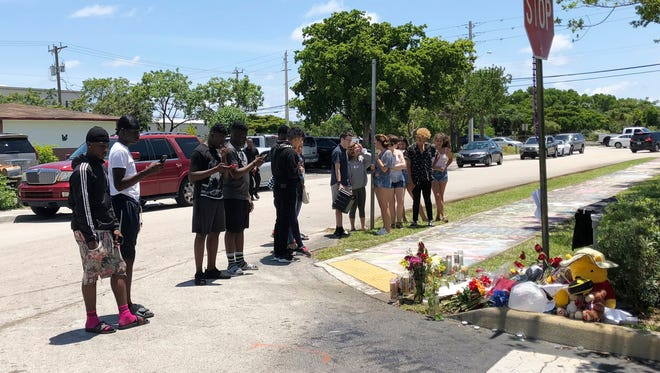 Fans and mourners of rap singer XXXTentacion pause by a memorial, June 19, 2018, outside Riva Motorsports in Deerfield Beach, Fla., where the rapper was killed the day before.