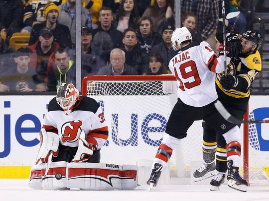 New Jersey Devils goalie Cory Schneider (35) makes a save while center Travis Zajac (19) battles with Boston Bruins center David Krejci (46) during the second period at TD Garden.