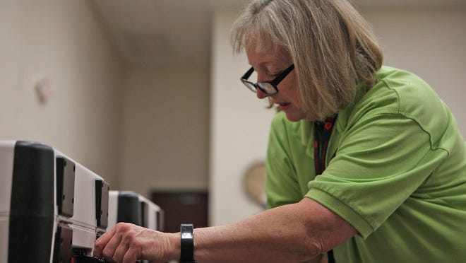 Tom Green County Election Administrator Vona Hudson sets up voting equipment at MHMR Services in San Angelo in March before the primary.