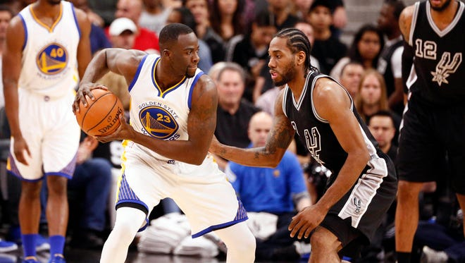 Golden State Warriors Draymond Green (23) is defended by San Antonio Spurs small forward Kawhi Leonard (2) in Sunday's game.